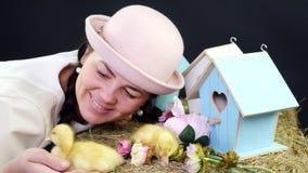 Портрет, милая молодая женщина с 2 отрезками провода и в смешной розовой шляпе играя с малыми желтыми утятами В файле акции видеоматериалы