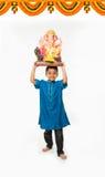 Портрет милого маленького индийского мальчика держа murti /statue идола Ganesh или ganesha или ganapati лорда над его головой, пр Стоковые Изображения