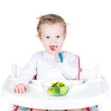 Портрет милого малыша есть брокколи в белом высоком стуле стоковая фотография