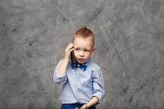 Портрет милого мальчика в голубых рубашке и бабочке с толпой Стоковые Изображения
