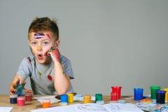 Портрет милого мальчика messily играя с красками Стоковая Фотография