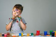 Портрет милого мальчика messily играя с красками Стоковое Изображение RF