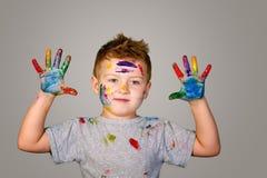 Портрет милого мальчика messily играя с красками Стоковые Изображения RF