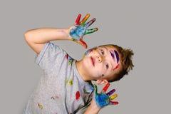 Портрет милого мальчика messily играя с красками Стоковые Изображения
