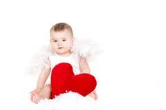 Портрет милого прелестного маленького ангела валентинки при красное мягкое сердце изолированное на белой предпосылке Стоковое Изображение