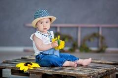 Портрет милого ребёнка на светлой предпосылке с венком цветков на ее голове сидя на корзине софы стоковые изображения