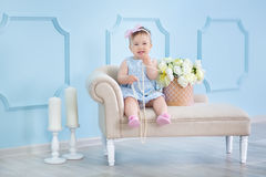 Портрет милого ребёнка на светлой предпосылке с венком цветков на ее голове сидя на корзине софы стоковые изображения rf