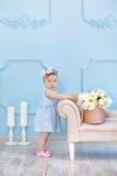 Портрет милого ребёнка на светлой предпосылке с венком цветков на ее голове сидя на корзине софы стоковое изображение