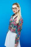 Портрет милой белокурой женщины при Ponytail нося красочную рубашку, белую юбку и Eyeglasses на голубой предпосылке Стоковое Изображение RF