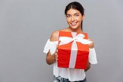 Портрет милой девушки давая подарочную коробку на камере Стоковое Изображение