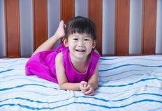 Портрет милой девушки лежа barefoot на кровати в спальне Стоковые Фотографии RF