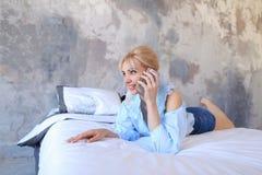 Портрет милой девушки, которая беседующ на сотовом телефоне и усмехаться, Стоковые Изображения