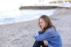 Портрет милой девушки которая усмехается и смотрится камеру, сидя дальше Стоковое Изображение