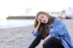 Портрет милой девушки которая усмехается и смотрится камеру, сидя дальше Стоковое Изображение RF