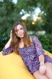 Портрет милой девушки сидя в стуле и усмехаясь в фотоснимке Стоковая Фотография