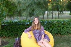 Портрет милой девушки сидя в стуле и усмехаясь в фотоснимке Стоковая Фотография RF