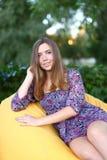 Портрет милой девушки сидя в стуле и усмехаясь в фотоснимке Стоковые Фото