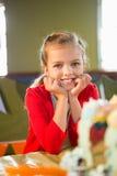 Портрет милой девушки сидя на таблице во время вечеринки по случаю дня рождения Стоковые Изображения