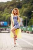 Портрет милой девушки с длинным вьющиеся волосы усмехаясь к камере в городе на bulding предпосылке Стоковое Изображение RF