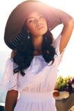 Портрет милой девушки с темными волосами в элегантной шляпе и белизна одевают Стоковые Фото