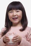 Портрет милой девушки с челками выпивая стекло молока с усиком молока Стоковые Фото