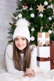 Портрет милой женщины лежа около украшенной рождественской елки Стоковое Изображение RF