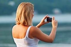 Портрет милой женщины принимая фото с мобильным телефоном Стоковое Фото