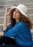 Портрет милой женщины сидя outdoors с шляпой Стоковые Изображения RF