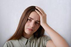 Портрет милой коричнев-наблюданной девушки и темных длинных волос нося зеленую рубашку утомляя выражение держа ее руку на голове  Стоковое Изображение