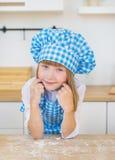 Портрет милой маленькой девочки в кашеваре смотрит на кухне Стоковое Фото