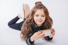 Портрет милой маленькой девочки кладя на пол с телефоном играть игр стоковое изображение