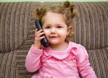 Портрет милой маленькой девочки на стуле говоря на телефоне стоковая фотография rf