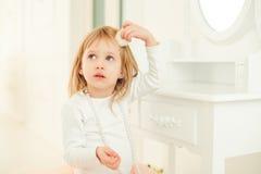 Портрет милой маленькой девочки сидя около зеркала в светлой комнате стоковые фото