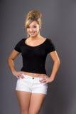Портрет милой молодой блондинкы, в белых шортах и темной верхней части на g Стоковое Изображение RF