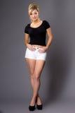 Портрет милой молодой блондинкы, в белых шортах и темной верхней части на g Стоковые Фото