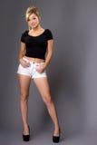 Портрет милой молодой блондинкы, в белых шортах и темной верхней части на g Стоковые Изображения