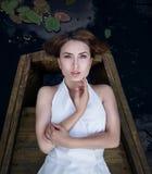 Портрет милой молодой женщины лежа в шлюпке на речном береге Стоковые Фото