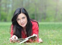 Портрет милой молодой женщины имея остатки с книгой на траве внутри Стоковая Фотография