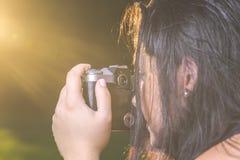 Портрет милой молодой женщины принимая фото с винтажной ретро камерой во время захода солнца Стоковые Изображения RF