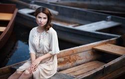 Портрет милой молодой женщины сидя в шлюпке на речном береге Стоковая Фотография