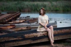Портрет милой молодой женщины сидя в шлюпке на речном береге Стоковые Фотографии RF