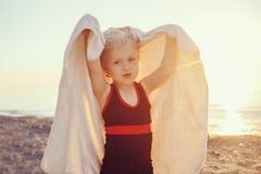 Портрет милой прелестной счастливой усмехаясь маленькой девочки малыша с полотенцем на пляже делая стороны представлений имея пот Стоковые Изображения