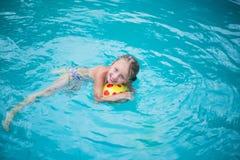 Портрет милой счастливой маленькой девочки имея потеху в бассейне Спорт малышей на каникуле лета семьи Активный здоровый праздник Стоковые Фото