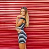 Портрет милой усмехаясь девушки стоя на красной предпосылке стены Стоковые Изображения