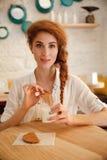 Портрет милой усмехаясь женщины redhead сидя на кафе Стоковые Изображения