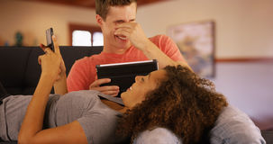 Портрет милых пар наслаждаясь часами досуга с приборами smartphone и таблетки Стоковое Изображение