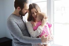 Портрет младенца молодой семьи утешая близко к окну стоковая фотография