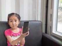 Портрет мобильного телефона игры маленькой девочки Азии милого Стоковые Фото