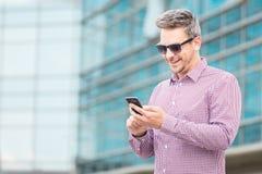 Портрет модного бизнесмена используя smartphone outdoors стоковые фотографии rf