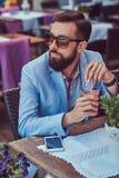 Портрет модного бородатого мужчины с стильной стрижкой, владения стекло капучино, сидя в кафе outdoors стоковое изображение rf